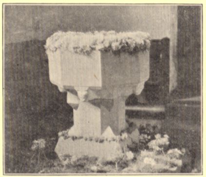 A black and white photograph, by Rev. Hilderic Friend, of a font decorated with flowers, for Easter, Bolton, Cumberland.