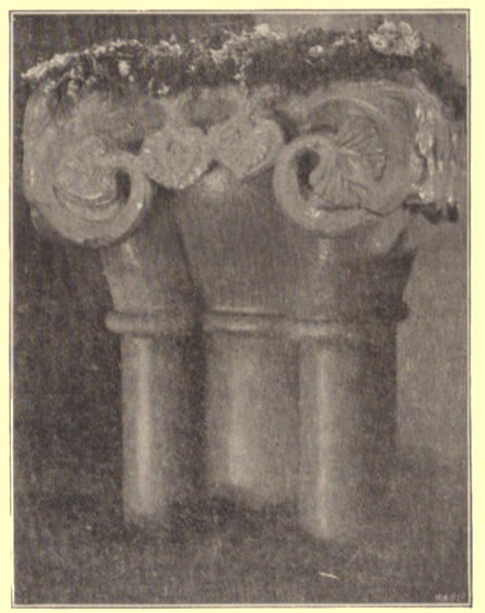 A black and white photograph, by Rev. Hilderic Friend, of a Roman font decorated with flowers, for Easter, Cross Canonby, Cumberland.