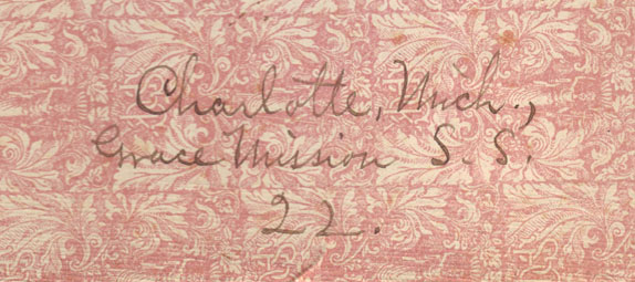 A portion of the other of the two front rose colored floral end-papers with the address; 'Michigan, Grace Mission S. S.'