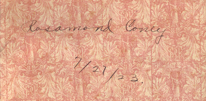 A portion of the rose-colored floral end-paper, from the front of the book, with the signature  and date in ink of a past owner: 'Rosamond Coney'.  The pages are yellower than on the facing sheet.