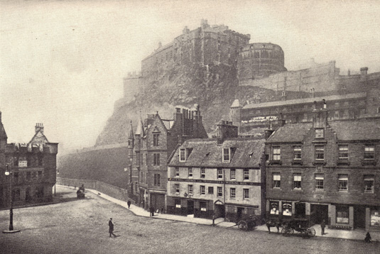 Black and white photograph of Edinburgh Castle in Scotland, on a hill surrounded with haze, taken from below that includes a clear view of a street and buildings, taken in the late 19th century.