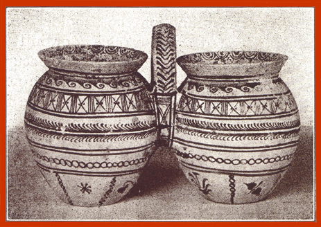 Black and white photograph of a decorated double clay vase, with a handle between them.