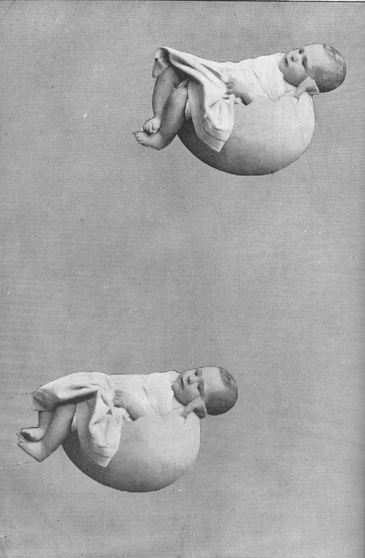 Black and white photograph of two babies each sleeping in half an eggshell suspended in mid-air. Early example of tricks and illusions of photography.