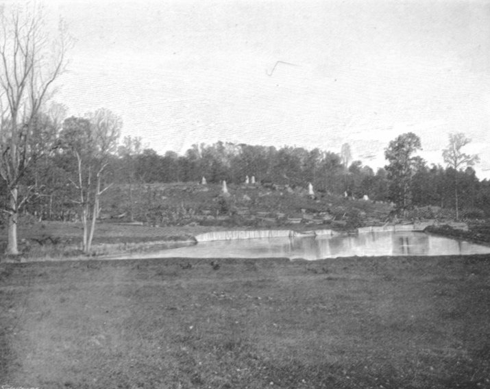 Black and white photograph of Round Top, showing a flat field, with some standing water and a small rise in the land beyond.