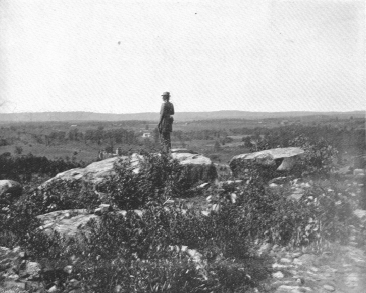 Black and white photograph of a statue of a Civil War Soldier in uniform on a hill overlooking lower lands.