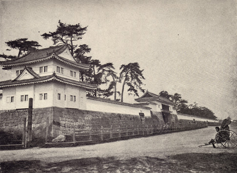 Black and white photograph of The Mikado's Palace in Japan, shown behind a low brick wall with a few trees behind it and a road with a figure in a Japanese cart on the road in front of it, taken in the late 19th century.