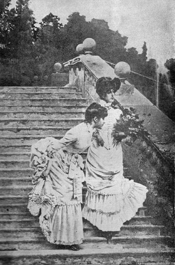 2 women in white Victorian dresses, including bustles, descending an outdoor stone staircase