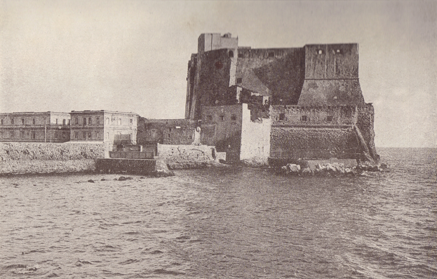 A black and white photograph, of the Castel del Ovo, with the ocean washing its base.