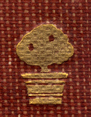 Decorated Adornment from the spine of the book, of a tree with gilt leaves on a burgundy woven ground.