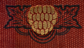 Decorated Adornment from the spine of the book, of a gilt berry with leaves in black around it on a burgundy woven ground.